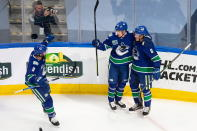 Vancouver Canucks' J.T. Miller (9), Elias Pettersson (40) and Brock Boeser (6) celebrate a goal against the Minnesota Wild during the second period of an NHL hockey playoff game in Edmonton, Alberta, Tuesday, Aug. 4, 2020. (Codie McLachlan/The Canadian Press via AP)