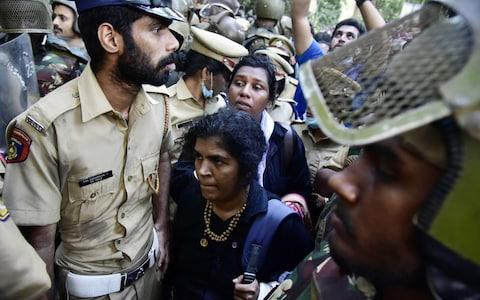 Two women breached a blockade surrounding a Hindu temple in the Indian state of Kerala, after the country's supreme court lifted a ban on women entering last September - Credit: AFP/Getty