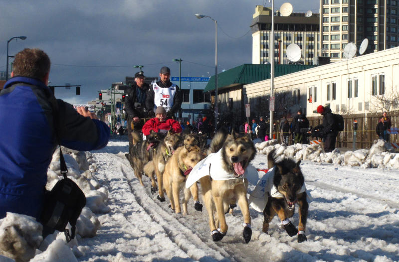FILE - In this March 7, 2015, file photo, musher Peter Kaiser, of Bethel, Alaska, leads his team past spectators during the ceremonial start of the Iditarod Trail Sled Dog Race, in Anchorage, Alaska. PETA is the biggest critic of the world's most famous sled dog race, but new Iditarod CEO Rob Urbach has started discussions with the animal rights group and plans a sit-down meeting with PETA, Thursday,  Oct. 17, 2019, in Los Angeles. (AP Photo/Rachel D'Oro, File)