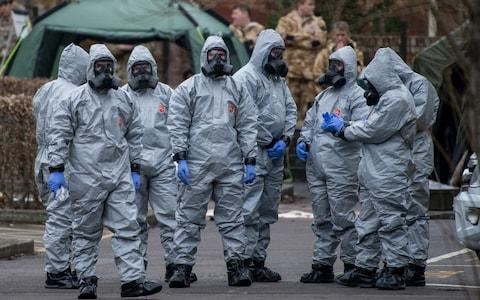 Military personnel wearing protective suits - Credit: Chris J Ratcliffe /Getty