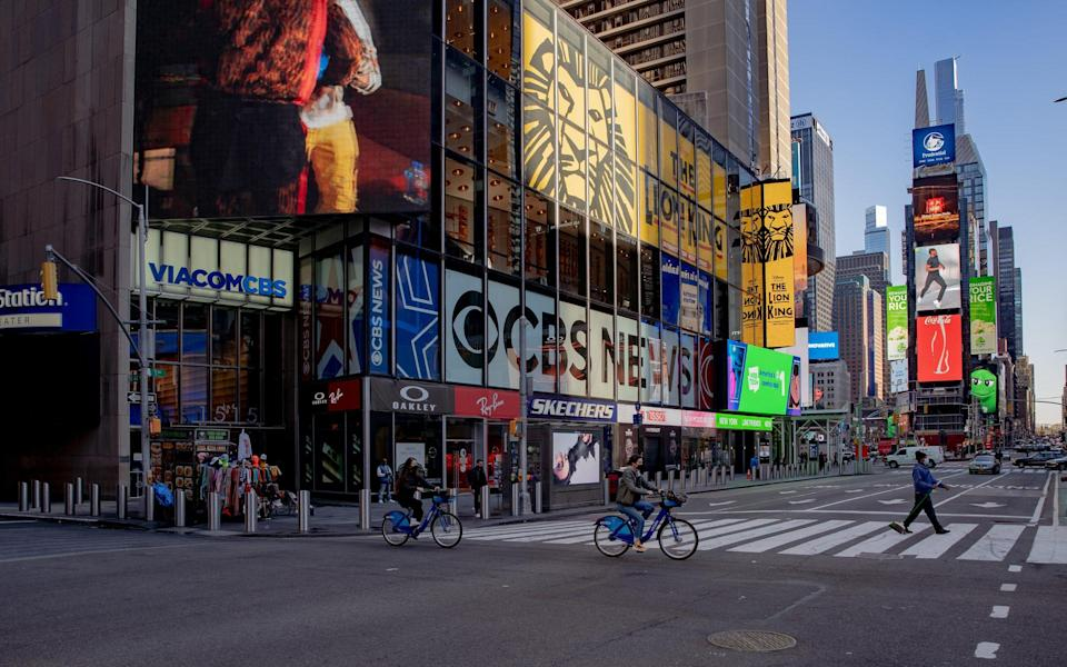 Cyclists cross a street in Times Square. New York City remains quiet as tourist numbers are down by two thirds. - Bloomberg