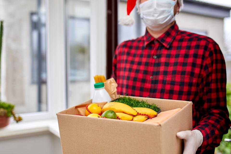 a man holding a box with food while wearing as mask and Santa hat