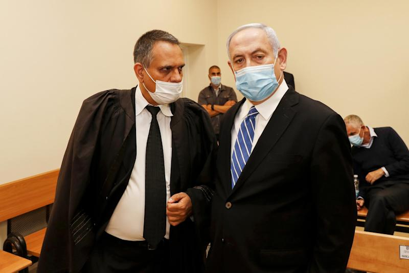 Israeli Prime Minister Benjamin Netanyahu (R), wearing a protective face mask, is pictured inside a courtroom at the district court of Jerusalem: RONEN ZVULUN/POOL/AFP via Getty Images