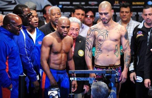 US boxer Floyd Mayweather (L) and Puerto Rico's Miguel Cotto eye the scale during Cotto's weigh-in on May 4, in Las Vegas, Nevada, on the eve of their Super Welterweight championship fight