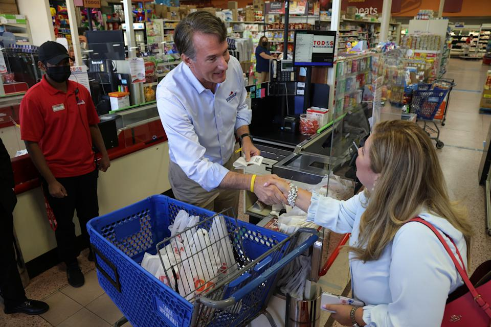Glenn Youngkin stands at a grocery store check-out counter and shakes hands with a customer, neither of whom wear face masks.