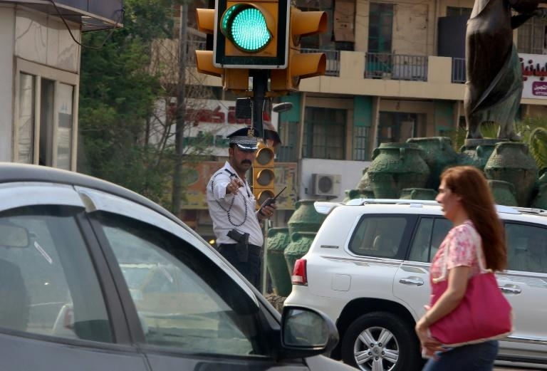 A policeman directs traffic in a street ot the capital of Iraq, a country where tribal customs can often take precedence over state law