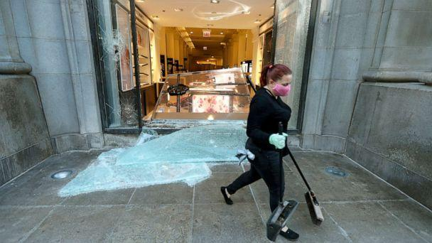 PHOTO: A volunteer worker walks past a shattered display window early, May 31, 2020, at the downtown Macy's store in Chicago, after a night of unrest and protests over the death of George Floyd, a black man who was in police custody in Minneapolis. (Charles Rex Arbogast/AP)