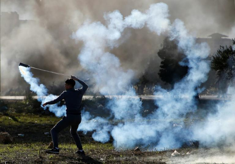 A Palestinian protester hurls a tear gas canister back towards Israeli troops during clashes in the West Bank city of Ramallah on December 8, 2017