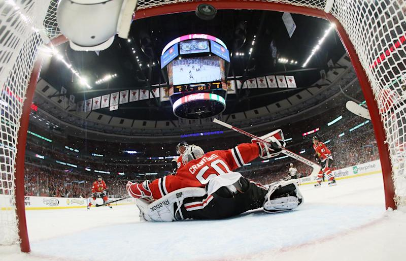 The puck flies into the net as Chicago Blackhawks goalie Corey Crawford (50) gives up a goal by Boston Bruins left wing Milan Lucic during the first period of Game 1 in their NHL Stanley Cup Final hockey series, Wednesday, June 12, 2013, in Chicago. (AP Photo/Bruce Bennett, Pool)