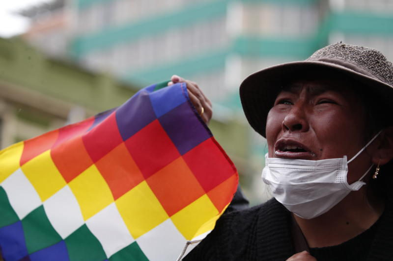 "A supporter of former President Evo Morales waves a ""wiphala"" flag that represents indigenous people, during a march of indigenous people entering La Paz, Bolivia, Tuesday, Nov. 12, 2019. Former President Evo Morales flew to exile in Mexico on Tuesday after weeks of violent protests, leaving behind a confused power vacuum in the Andean nation. (AP Photo/Natacha Pisarenko)"