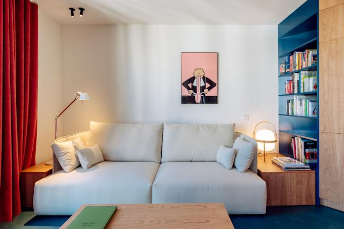 A white Joquer sofa allows surrounding colors (and a cheeky print by French illustrator Jean Jullien) to pop.