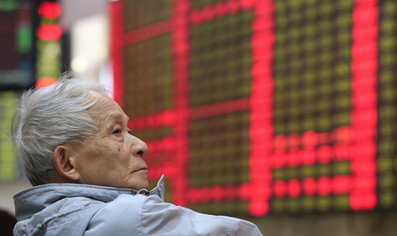 An investor looks at the stock price monitor at a private securities company in Shanghai, China, Wednesday, Dec. 11, 2013. Asian stocks were mostly down Wednesday as investors factored in the prospect of the Federal Reserve reducing its lavish monetary stimulus this month. (AP Photo)