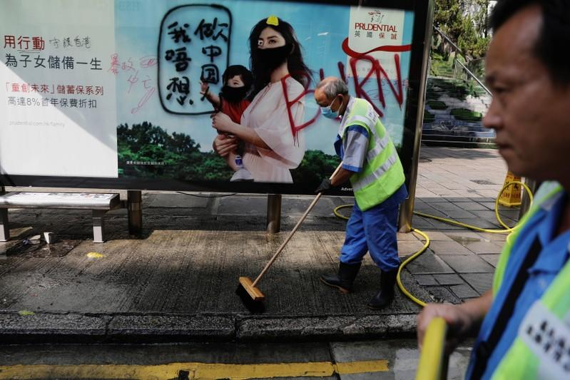 Cleaners wash a vandalized bus stop outside Kowloon Masjid and Islamic Centre in Hong Kong's tourism district Tsim Sha Tsui