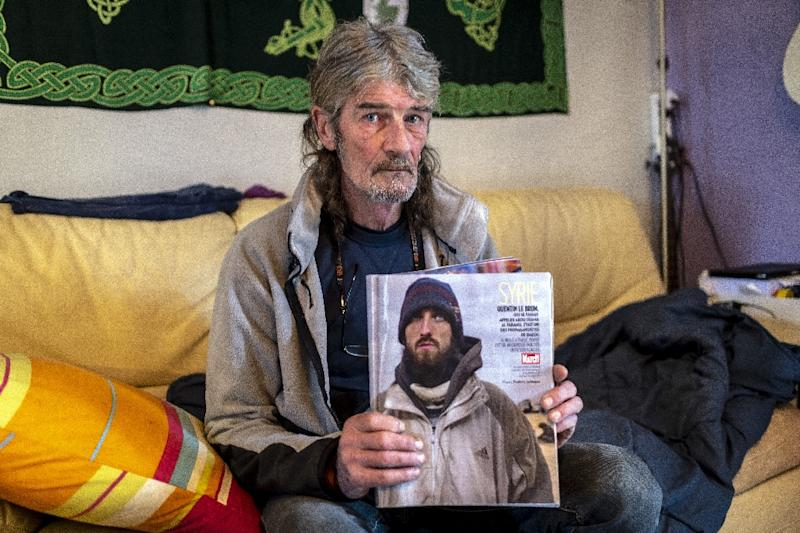 Jacques Le Brun holding a magazine picture of his son Quentin, who left to join the Islamic State in Syria in 2014, at the family home in Labastide-Rouairoux, southern France (AFP Photo/ERIC CABANIS)