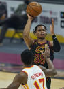 Cleveland Cavaliers' Isaac Okoro (35) shoots over Atlanta Hawks' Onyeka Okongwu (17) in the first half of an NBA basketball game, Tuesday, Feb. 23, 2021, in Cleveland. (AP Photo/Tony Dejak)