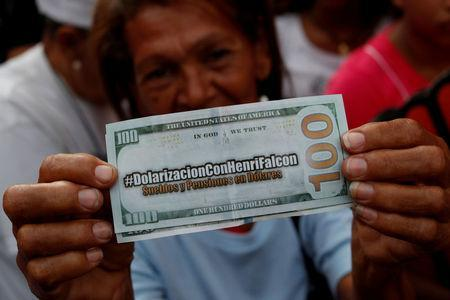 """FILE PHOTO: A supporter of Venezuelan presidential candidate Henri Falcon, holding a fake hundred dollar bill that reads, """"Dollarization with Henri Falcon"""" and """"Salaries and pensions in dollars"""", takes part in a campaign rally in Caracas, Venezuela May 14, 2018. REUTERS/Carlos Garcia Rawlins/File Photo"""