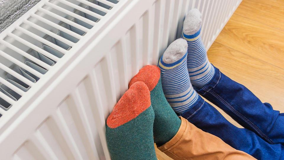 Woman and child wearing colorful pair of woolly socks warming cold feet in front of heating radiator in winter time.