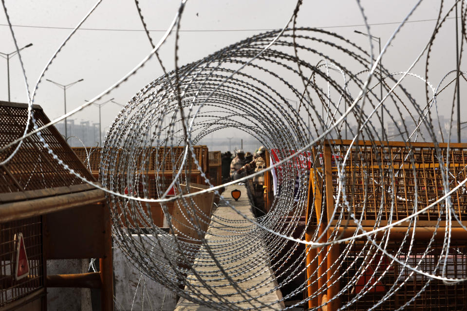 Indian para-military force soldiers stand against layers of barricades at Delhi-Utttar Pradesh border, in New Delhi, India, Tuesday, Feb. 2, 2021. Indian authorities Tuesday heavily ramped up security along three main protest sites outside New Delhi's border, using cemented iron spikes, steel barricades and deployed hundreds of police in riot gear in their latest attempt to thwart the growing farmers' protest on the edges of the capital. (AP Photo/Manish Swarup)