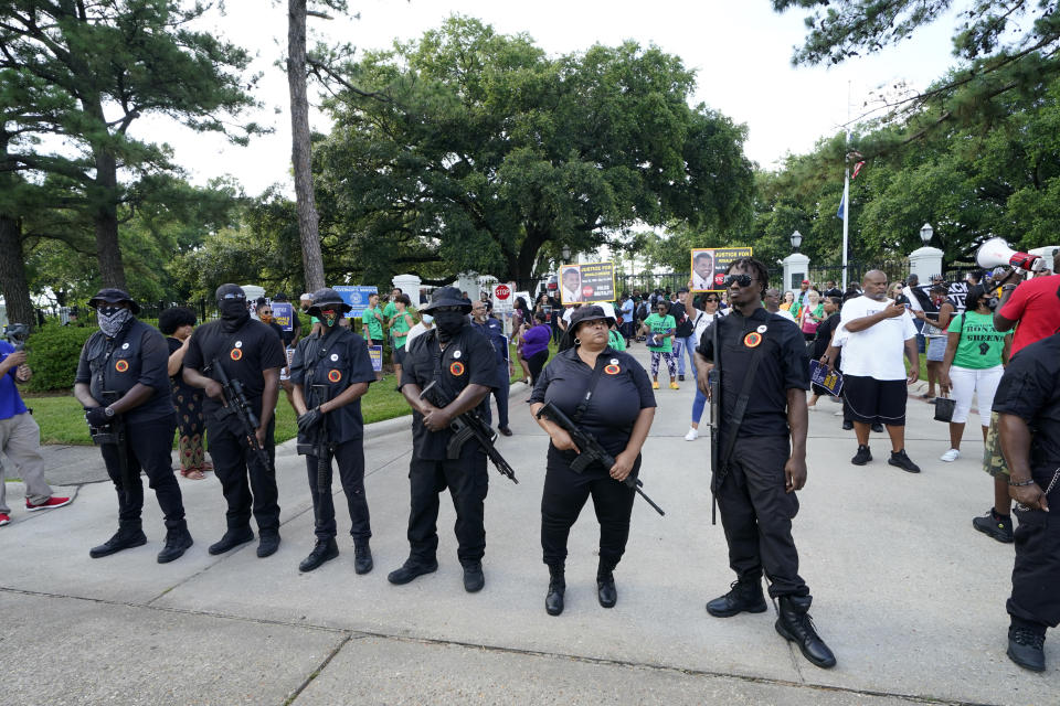 Members of the New Black Panther Party stand in front of the governor's mansion after a march from the state Capitol, Thursday, May 27, 2021, in Baton Rouge, La., protesting the death of Ronald Greene, who died in the custody of Louisiana State Police in 2019. (AP Photo/Gerald Herbert)