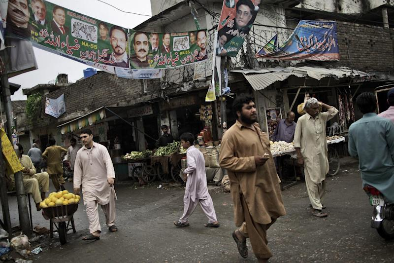 Pakistanis walk under election banners showing former prime minister, leader of Pakistan Muslim League-N, Nawaz Sharif, and other members of his party, in Rawalpindi, Pakistan, Sunday, May 12, 2013. Pakistan's former prime minister Nawaz Sharif looked set Sunday to return to power for a third term, with an overwhelming election tally that just weeks ago seemed out of reach for a man who had been ousted by a coup and was exiled abroad before clawing his way back as an opposition leader. (AP Photo/Muhammed Muheisen)
