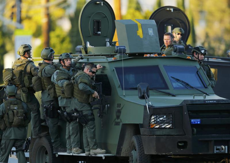 Police officers conduct a manhunt after a mass shooting in San Bernardino, California December 2, 2015. Gunmen opened fire on a holiday party on Wednesday at a social services agency in San Bernardino, California, killing 14 people and wounding 17 others, then fled the scene, triggering an intense manhunt and a shootoutout with police, authorities said.   REUTERS/Mike Blake