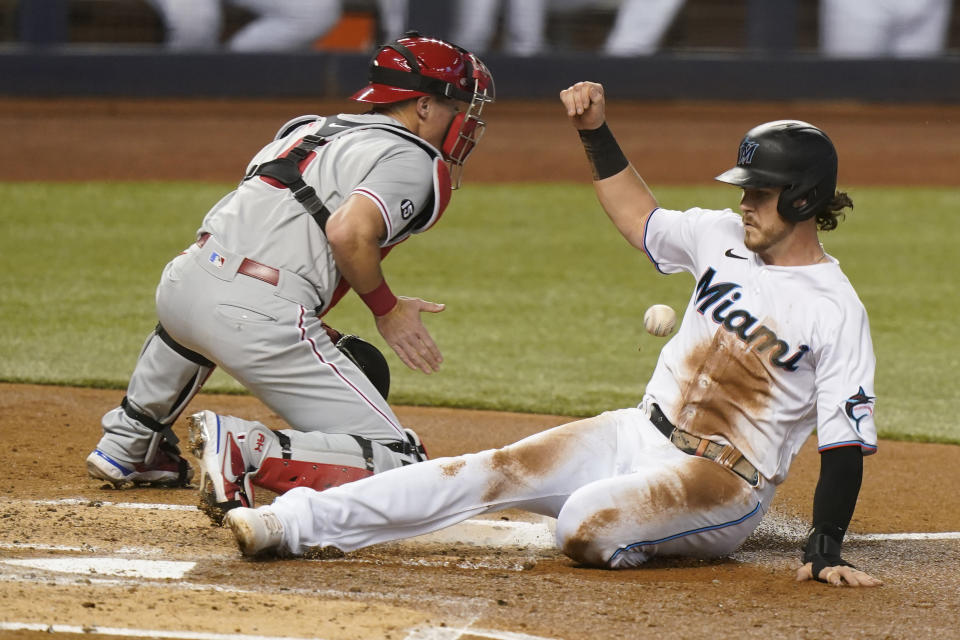 Miami Marlins' Brian Anderson, right, is safe at home on a sacrifice fly by Sandy Leon as Philadelphia Phillies catcher Andrew Knapp waits for the throw during the second inning of a baseball game, Monday, May 24, 2021, in Miami. (AP Photo/Wilfredo Lee)