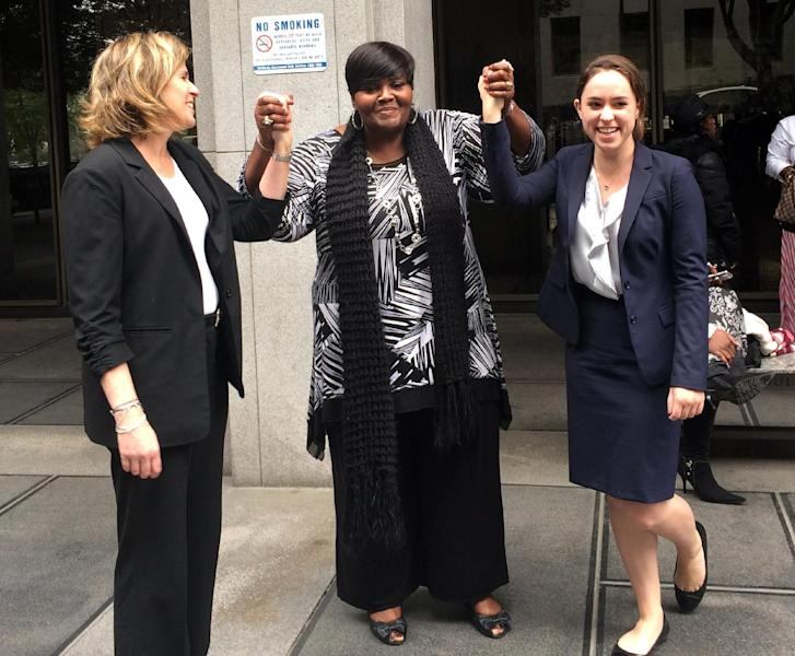 In this photo taken on Monday, March 24, 2014 and released by the University of Southern California Gould School of Law, USC Post-Conviction Justice Project attorneys, Heidi Rummel, left, and Laura Donaldson, right, celebrate with Mary Virginia Jones' daughter, Denitra Jones-Goodie, outside Superior court in Los Angeles. Mary Virginia Jones, a 74-year-old California woman, was freed late Monday after serving 32 years of a life sentence for her role in a 1981 killing. Los Angeles County prosecutors conducted a new investigation and agreed to accept a plea of no contest for involuntary manslaughter. Judge William C. Ryan ruled Monday afternoon that Jones had served well over the 11-year maximum sentence for the lesser crime and ordered her freed. (AP Photo/USC Gould School of Law, Jilien Silsby)