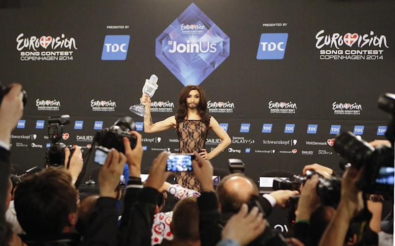 Singer Conchita Wurst representing Austria who performed the song 'Rise Like a Phoenix' holds up the trophy during a press conference after winning the Eurovision Song Contest in the B&W Halls in Copenhagen, Denmark, Saturday, May 10, 2014.(AP Photo/Frank Augstein)