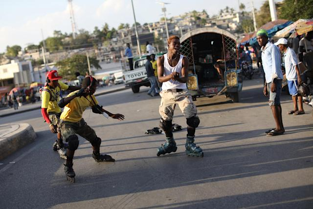 Youths slide as they brake after skating down a street in Port-au-Prince, Haiti, March 18, 2018. REUTERS/Andres Martinez Casares