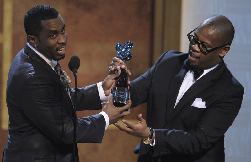 "FILE - In this Jan. 16, 2010 file photo, media executive Andre Harrell, right, presents an award to Sean ""Diddy"" Combs at the Warner Theatre during the 2010 BET Hip Hop Honors in Washington. Harrell, the Uptown Records founder who shaped the sound of hip-hop and R&B in the late '80s and '90s with acts like Mary J. Blige and Heavy D and also launched the career of mogul Sean ""Diddy"" Combs, has died, several members of the music community revealed late Friday, May 8, 2020. He was 59. (AP Photo/Nick Wass)"