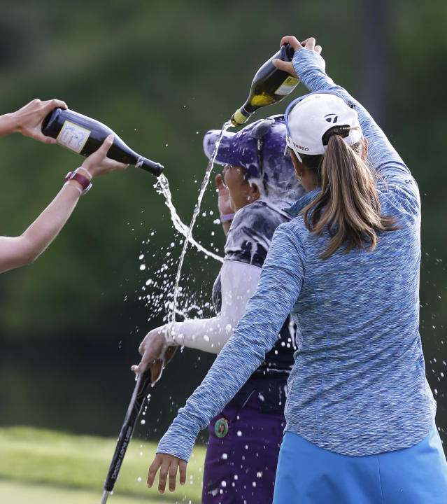 Lizette Salas is doused by fellow golfer Nina Hrigae, right, as she celebrates winning the Kingsmill Championship golf tournament at the Kingsmill resort in Williamsburg, Va., Sunday, May 18, 2014. Salas won her first LPGA event after shooting an even par-71 leaving her at 13-under for the tournament. (AP Photo/Steve Helber)