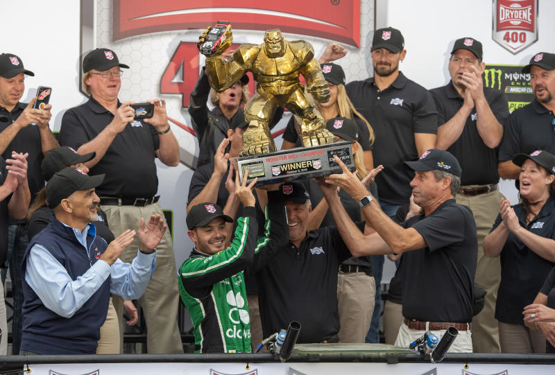 Kyle Larson, front left center, gets help in holding up the trophy after his win in the NASCAR Cup Series auto race Sunday, Oct. 6, 2019, at Dover International Speedway in Dover, Del. (AP Photo/Jason Minto)