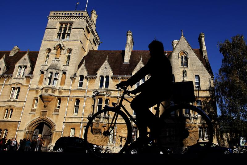 A cyclist is silhouetted in front of Balliol College, founded in 1263, it is one of the oldest constituent colleges of Oxford University in Oxford, England, Friday, Oct. 17, 2008. (AP Photo/Kirsty Wigglesworth)