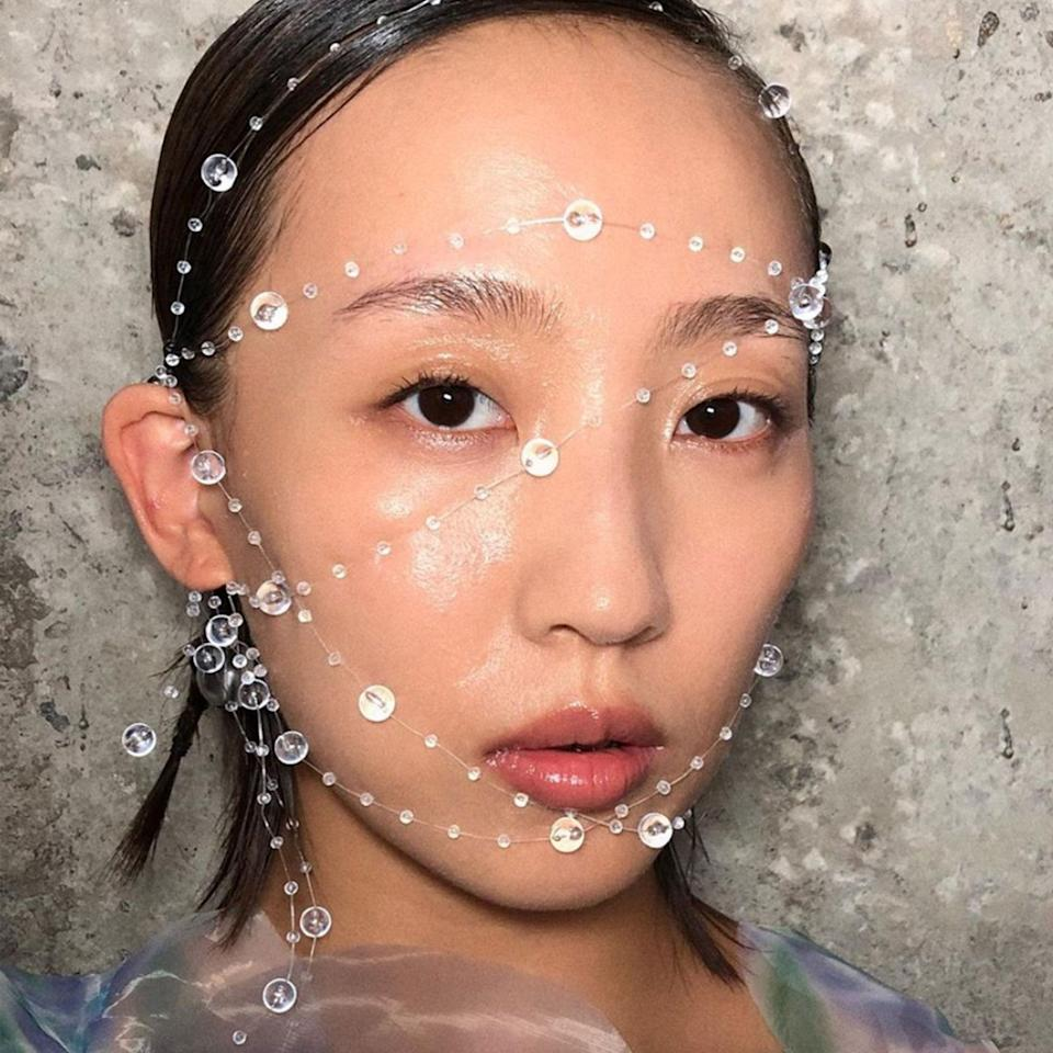 """Although <a href=""""https://www.instagram.com/valentina1121li/"""" rel=""""nofollow noopener"""" target=""""_blank"""" data-ylk=""""slk:Valentina Li"""" class=""""link rapid-noclick-resp"""">Valentina Li</a> identifies as a face painter, none of her beloved designs were brushed on for the look at Susan Fang. Instead, she amplified the glow of the models' complexions for a wet, dewy finish before delicately stringing water droplet-like beads around their faces and heads. The models' hair was also pulled back into sculptural buns by hairstylist <a href=""""https://www.instagram.com/Xuyouhua/"""" rel=""""nofollow noopener"""" target=""""_blank"""" data-ylk=""""slk:Youhua Xu"""" class=""""link rapid-noclick-resp"""">Youhua Xu</a>."""