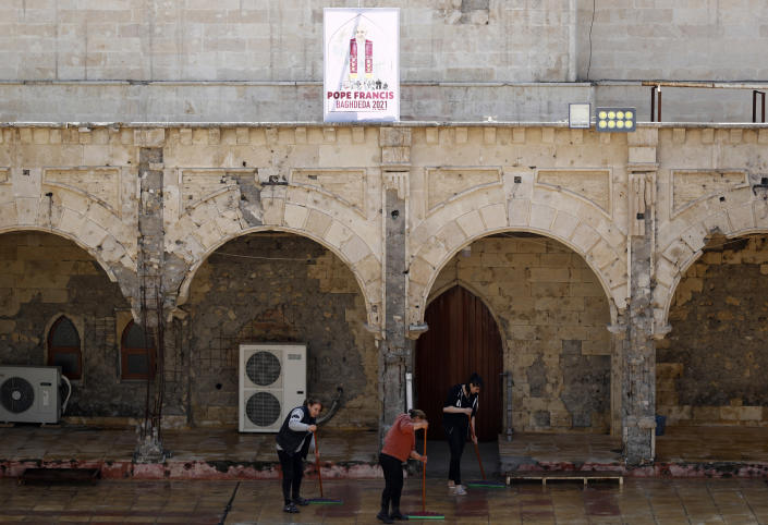 Iraqi Christians clean the Church of the Immaculate Conception in Qaraqosh, Iraq, Tuesday, Feb. 23, 2021. Pope Francis will visit the church during his historic trip to Iraq. Damaged during the Islamic State reign of terror, the church's tragedy mirrored that of its Christian community which was devastated by the group. (AP Photo/Hadi Mizban)