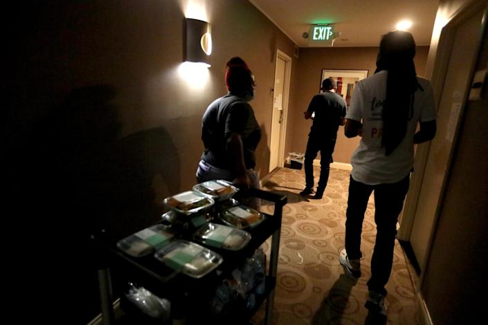 Mia Rogers, 23, left, delivers lunches to guests at an L.A. hotel participating Project Roomkey on July 22.