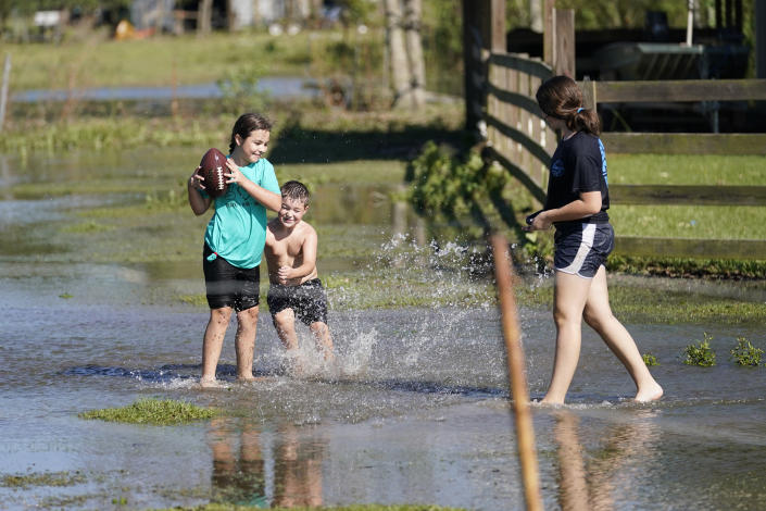 Siblings Chancy, left, Blayke, center, and Alayna Trahan, play in a field that was flooded from Hurricane Delta, at their home in Hayes, La., Saturday, Oct. 10, 2020. (AP Photo/Gerald Herbert)