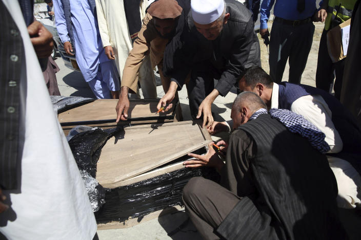 Families identify the bodies of their relatives who drowned after their boat sank on Turkey's Lake Van, at the Hamid Karzai International Airport in Kabul, Afghanistan, Wednesday, July 22, 2020. The boat sank last month while ferrying dozens of migrants across a lake in eastern Turkey. (AP Photo/Rahmat Gul)
