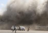 People react as dust rises after explosions hit Aden airport, upon the arrival of the newly-formed Yemeni government in Aden
