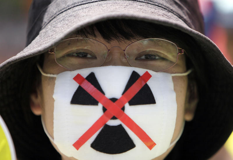 """An anti-nuclear protester waits to begin a march through downtown Tokyo Monday, July 16, 2012. Tens of thousands of people gathered at a Tokyo park, demanding """"Sayonara,"""" or goodbye, to nuclear power as Japan prepares to restart yet another reactor, and expressed outrage over a report that blamed culture on the Fukushima disaster. (AP Photo/Greg Baker)"""