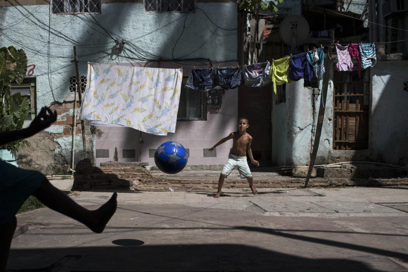 Igor Meireles, 8, center, plays goalkeeper as he prepares to block a kick from his brother Iago Meireles, 10, during their soccer game in the small square next to their home in Rio de Janeiro, Brazil, Sunday, March 16, 2014. The brothers took turns being the goalkeeper because neither wanted to play that position. With so many outstanding strikers and midfielders in Brazilian history, few chose goalkeepers as their childhood idols. (AP Photo/Felipe Dana)