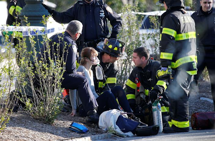 First responders assist a womaninjured on the bike path.