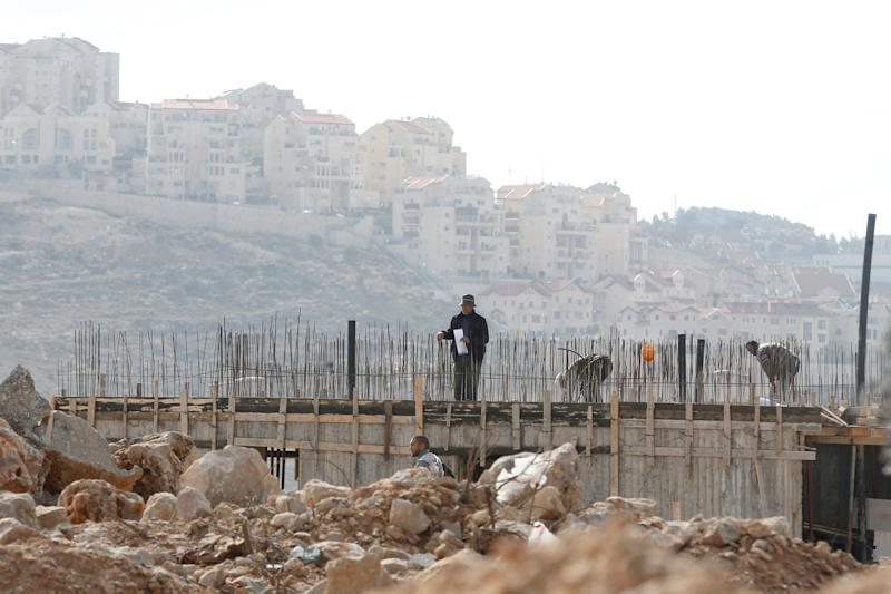 Palestinian labourers work at a construction site in the Israeli settlement of Efrat in the occupied West Bank