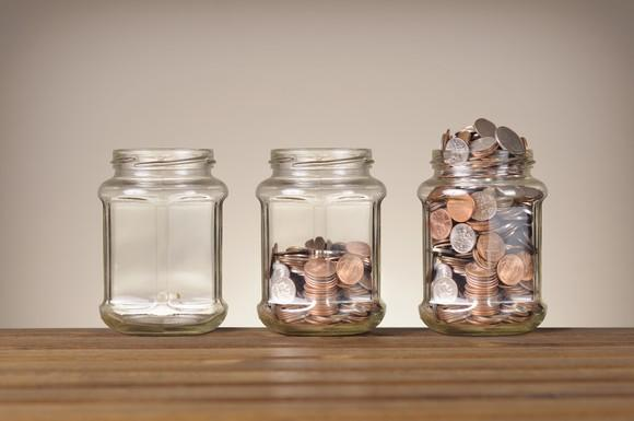 Empty jar, jar half-full of coins, and overflowing jar of coins.