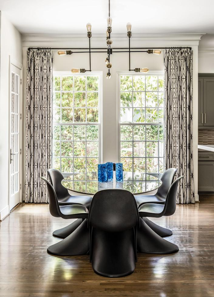 Set off the family room and kitchen, the breakfast area features a classic midcentury table by Room & Board, era-appropriate molded plastic chairs by Design Within Reach, and lighting from Wayfair. The curtains pop in every room; here they are made with a Kelly Wearstler fabric.