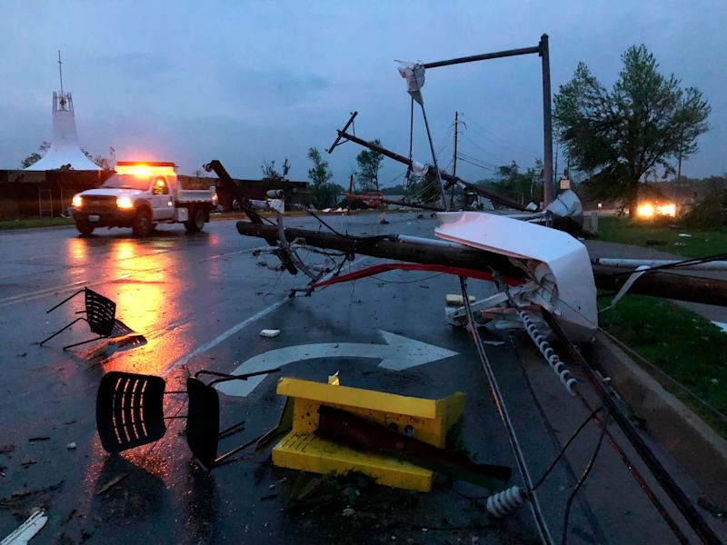 Plastic chairs lie in the road and metal from a damaged gas station roof is twisted around a downed power line in Jefferson City, Mo., on May 23, 2019. (Photo: AP Photo/David A. Lieb)