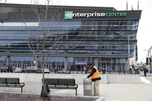 A worker cleans a trash can outside of Enterprise Center, home of the St. Louis Blues hockey team, Friday, March 13, 2020, in St. Louis. The NHL season has been suspended and the NCAA basketball tournament, which was scheduled to be held in the arena next week, has been cancelled in an effort to contain the COVID-19 virus. (AP Photo/Jeff Roberson)