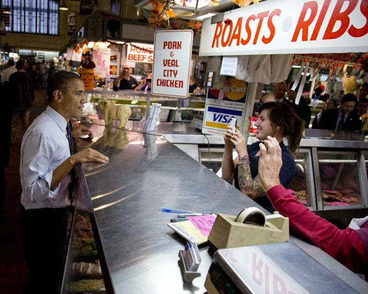 President Barack Obama pauses for a photograph as he greets people at West Side Market, Friday, Oct. 5, 2012, in Cleveland. (AP Photo/Carolyn Kaster)