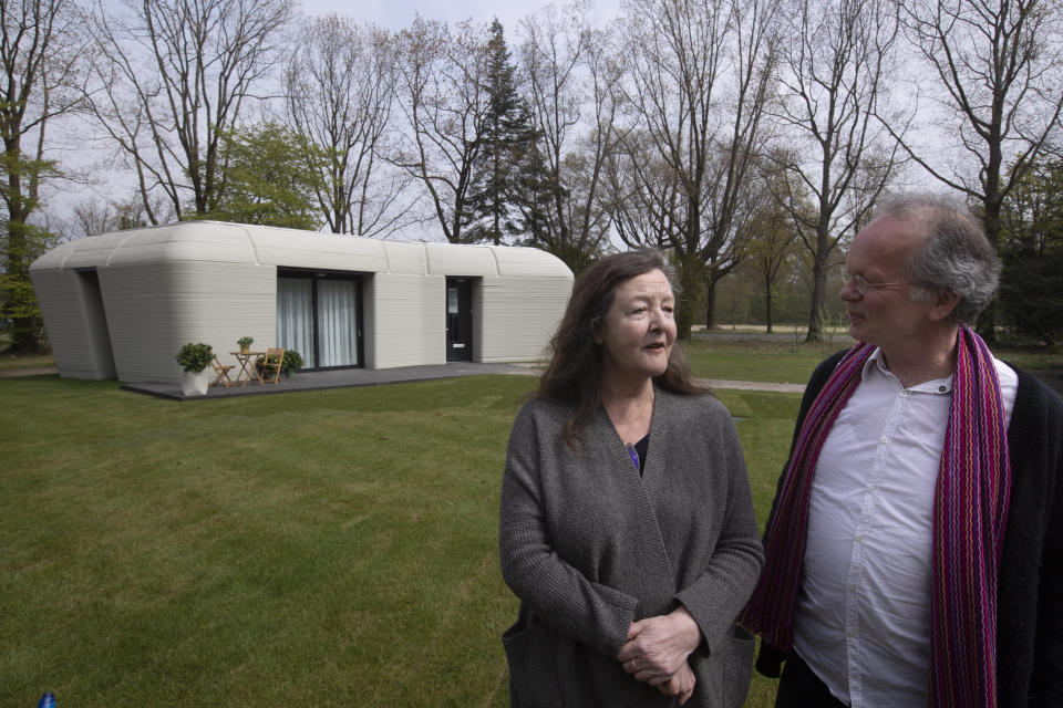 Tenants Elize Lutz, left, and Harrie Dekkers' new home is a 94-square meters (1,011-square feet) two-bedroom bungalow resembling a boulder with windows in Eindhoven, Netherlands, Friday, April 30, 2021. The fluid, curving lines of its gray walls look natural. But they are actually at the cutting edge of housing construction in the Netherlands and around the world. They were 3D printed at a nearby factory. (AP Photo/Peter Dejong)