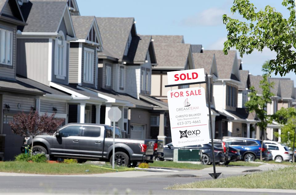A realtor's for sale sign stands outside a house that had been sold in Ottawa, Ontario, Canada, May 27, 2021.  REUTERS/Patrick Doyle
